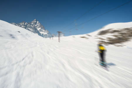 bardonecchia: Skiing on snowy slope in scenic ski resort of the italian Alps, with bright sunny day of spring season and high mountain peak in the background. Radial blurred motion effect applied. Stock Photo