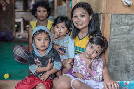pobreza: Loko, Sulawesi, Indonesia - 17 de agosto 2014: Retrato de interior de una familia linda, dos mujeres adultas y dos bebés, en el pueblo de Loko, región Mamasa, West Tana Toraja.