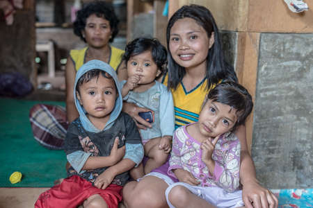 indonesia culture: Loko, Sulawesi, Indonesia - August 17, 2014: Indoor portrait of a cute family, two adult women and two babies, in the village of Loko, Mamasa region, West Tana Toraja.