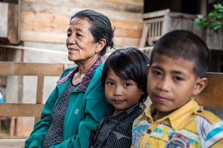 indonesia culture: Loko, Sulawesi, Indonesia - August 17, 2014: Selective focus on a wrinkled senior woman with pair of children out of focus in the village of Loko, Mamasa region, West Tana Toraja, South Sulawesi, Indonesia.