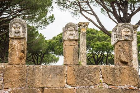 escultura romana: Los detalles de la escultura máscara romana, probablemente, la decoración del teatro en la antigua ciudad de Ostia, Roma, Italia, montan hoy sobre los restos de la pared de la scaena.