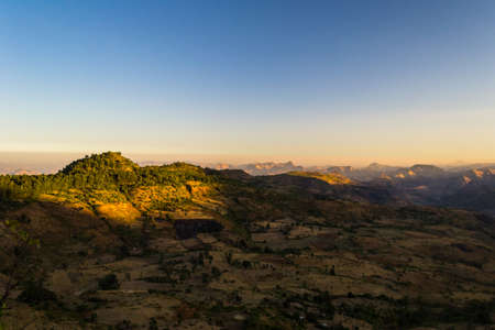 east africa: Wide angle view from the Simien Mountains on valleys and highlands in Tigray region, hit by the first golden sunlight. Northern Ethiopia, East Africa.