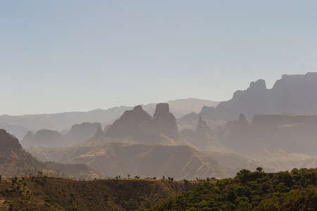 telephoto: Telephoto view from the Simien Mountains National Park on the misty valleys, the silhouette of the rocky pinnacles and the barren highlands of the Tigray region. North Ethiopia, East Africa.
