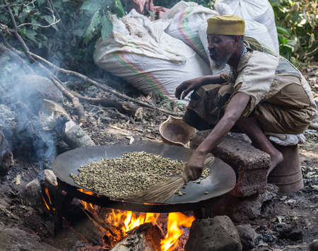 Bahir Dar, Ethiopia - January 18, 2012: Unidentified ethiopian person in poor clothings roasting coffee beans in a large pan placed on a wood fire in Bahir Dar, Ethiopia. Outdoor setting.