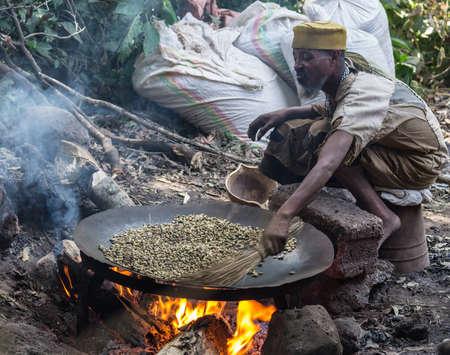 hombre tomando cafe: Bahir Dar, Etiopía - 18 de enero 2012: persona etíope no identificada en ropas pobres granos de café tostado en una sartén grande colocado sobre un fuego de leña en Bahir Dar, Etiopía. Escenario al aire libre. Editorial