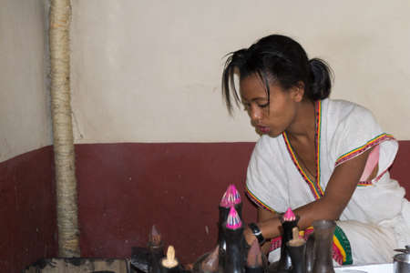ethiopian ethnicity: Bahir Dar, Ethiopia - January 18, 2012: Cute ethiopian young woman in traditional clothings performing a traditional coffee ceremony in Bahir Dar, Ethiopia. Indoor setting, natural light.