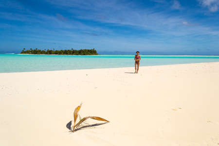 scenic background: Woman walking on white beach in idyllic scenic background of turquoise sea and remote desert island. Atoll of Aitutaki, Cook Islands. Stock Photo
