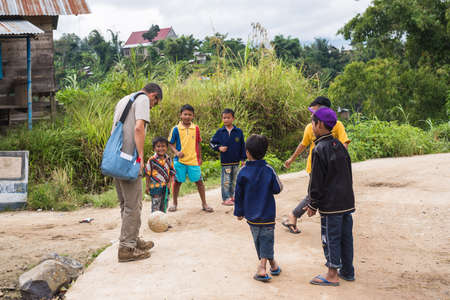 european ethnicity: Osango, Indonesia - August 17, 2014: Group of unidentified funny children of indonesian ethnicity playing football with adult european man in the village of Osango, Mamasa region, Sulawesi, Indonesia.