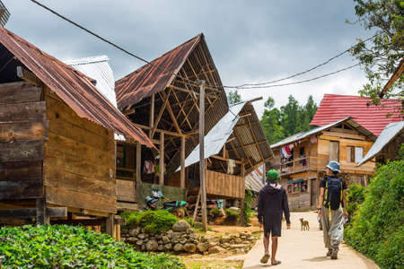 indonesia culture: Taupe, Indonesia - August 16, 2014: Backpacker visiting the traditional village of Loko in the hilly region of Mamasa, West Tana Toraja, remote but upgrowing travel destination in South Sulawesi, Indonesia.