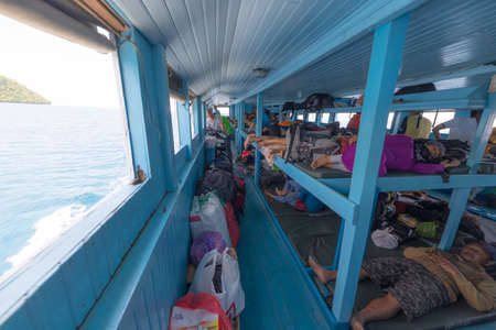 navigating: Ampana, Indonesia - August 23, 2014: People sitting or lying on the benches of an obsolete passenger ship while navigating to the Togean (or Togian) Islands, Central Sulawesi, Indonesia. Concept of travel safety in developing countries. Editorial