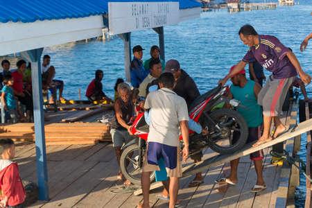 Desa Tongkabo, Indonesië - 23 augustus 2014: Groep van de lokale bevolking uitstappen een scooter veerboot in de haven van desa Tongkabo, Togian Islands, Sulawesi, Indonesië.