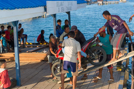 Desa Tongkabo, Indonesia - August 23, 2014: Group of local people disembarking a scooter from ferry boat in the port of Desa Tongkabo, Togian Islands, Sulawesi, Indonesia.