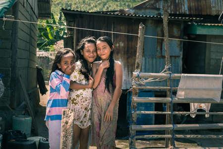 Boneoge, Indonesië - 31 augustus 2014: Portret van drie lachende meisjes met een slechte kleding in het shanty dorp Boneoge, Centraal-Sulawesi, Indonesië. Concept van de armoede en de jeugd in develping landen.