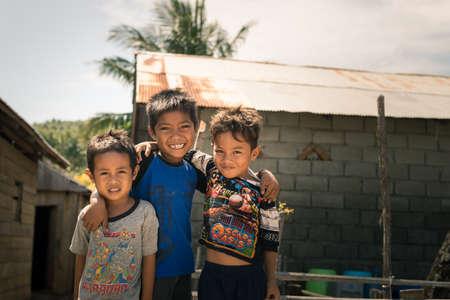 Boneoge, Indonesië - 31 augustus 2014: Portret van drie lachende jongens met een slechte kleding in het shanty dorp Boneoge, Centraal-Sulawesi, Indonesië. Concept van de armoede en de jeugd in develping landen.