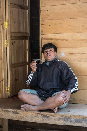 crossed cigarette: Osango, Sulawesi, Indonesia - August 17, 2014: Portrait of young man sitting cross legged and smoking a cigarette in the village of Osango, Mamasa region, West Tana Toraja, Sulawesi, Indonesia. Editorial