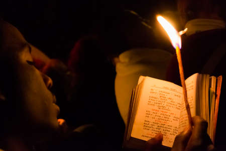 Gonder, Ethiopia - January 20, 2012: priest holding a candle in the night and reading a book written in the old language of the church, called Geez, during the Timkat holiday, the important Ethiopian Orthodox celebration of Epiphany.