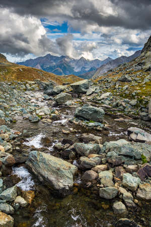 High altitude flowing stream in harsh rocky landscape with scenic dramatic stormy sky. Wide angle view from above. photo
