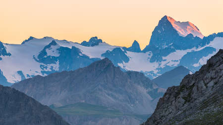 Last red sunlight hitting the glacier on the majestic peak of the Barre des Ecrins (4101 m), France. Telephoto view from distant at high altitude. Clear orange sky.