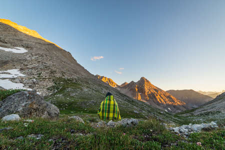 high up: One unrecognizable person covered by blanket  sitting and watching sunset high up in the Alps. Wide angle view from above with flowering meadow in the foreground and glowing mountain peaks in the background.