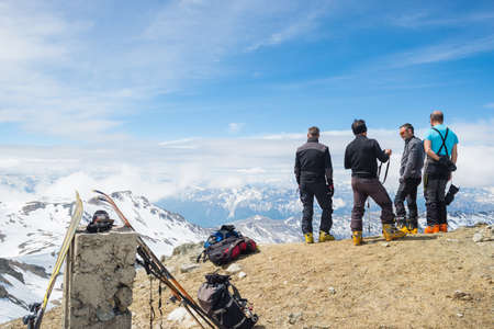 bardonecchia: Bardonecchia, Italy - May 23, 2015: Group of four alpinists chatting in scenic high altitude background on the M. Sommeiller summit (3333 m) in the italian french Alps in a sunny day of springtime. Concept of success and conquering the top.