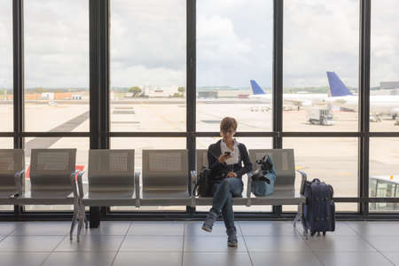 landline: Business woman sitting in airport terminal with suitcase and waiting for departure while using mobile phone. Concept of people sharing informations with new technology while traveling.