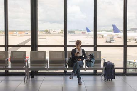 femme valise: Femme d'affaires assis dans terminal de l'a�roport avec une valise et en attente de d�part tout en utilisant un t�l�phone mobile. Concept de personnes vivant informations avec la nouvelle technologie tout en voyageant.