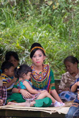 adult indonesia: Sangalla, Indonesia - September 8, 2014: Portrait of young adult woman of Toraja ethnicity in traditional attire sitting and embracing little girl in Sangalla, Sulawesi, Indonesia.