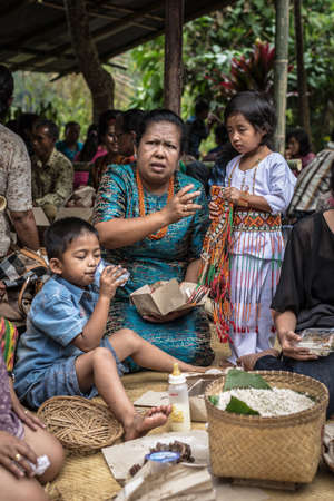 mother and teen daughter: Sangalla, Indonesia - September 8, 2014: Children with mature woman of Toraja ethnicity in traditional attire having meal in Sangalla, Sulawesi, Indonesia.