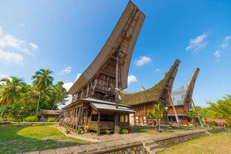 Rij van traditionele huizen in een typisch traditioneel dorp van Tana Toraja, Zuid Sulawesi, Indonesië. Groothoek oog van onderen in een heldere dag van de zomer. Uitstekende lokale architectuur, boot vormige dak en een traditionele inrichting.