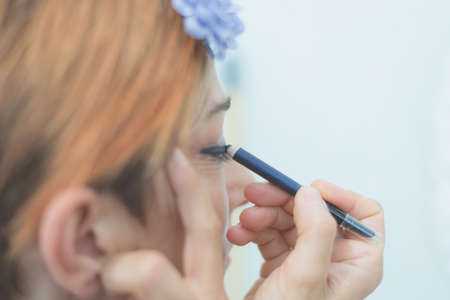 and eyelid: Mature woman applying eyeliner on eyelid with blue pencil. Neutral background, toned image, decontrasted. Selective focus, very shallow depth of field. Stock Photo