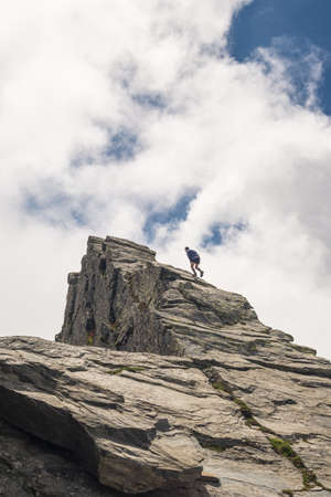 conquering: Hiker climbing on steep rocky slope towards the mountain summit without protection. Dramatic cloudy sky. Concept of reaching the goal and conquering the success.