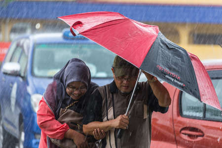wet men: Kuching, Malaysia - August 10, 2014: Couple of people sheltering under umbrella while raining in the streets of Kuching, West Sarawak, Borneo, Malaysia.