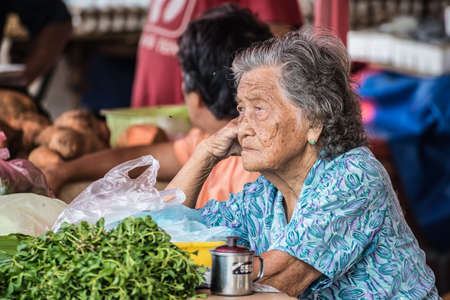 Kuching, Malaysia - August 10, 2014: Portrait of a bored senior woman managing a vegetable market stall in the popular Satok Weekend Market in Kuching, Borneo, Malaysia. Editorial