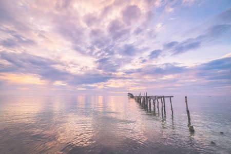 blurred motion: Old and damaged wooden jetty with romantic colorful cloudscape at dusk on the coastline of Sulawesi, Indonesia. Wide angle shot, long exposure, blurred motion. Marsala toned image, vignetting added. Stock Photo