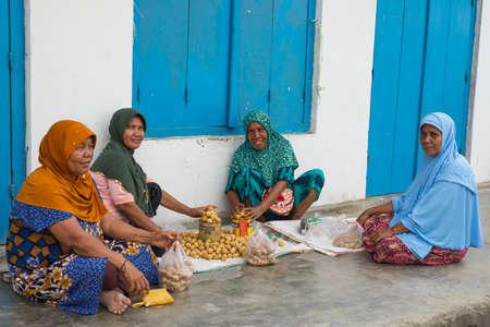 Ampana, Indonesië - 29 augustus 2014: De niet geïdentificeerde groep van vrouwen het dragen van hijab en traditionele kleding verkopen van tropisch fruit in de straat van Ampana, Centraal-Sulawesi, Indonesië. Concept van de lokale levensstijl en traditionele culturen. Redactioneel