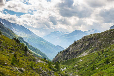 dramatic sky: Dramatic sky in amazing green alpine valley in spring season. Wide angle view from above in the italian french Alps.