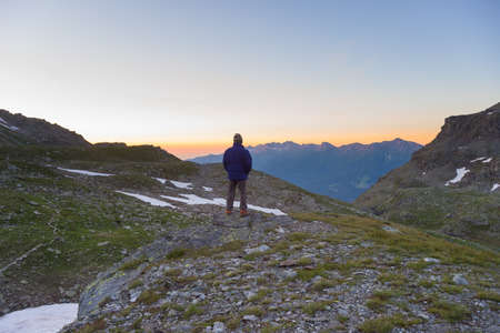high up: One person standing on rocky terrain and watching a colorful sunrise high up in the Alps. Wide angle view from above with glowing mountain peaks in the background. Summer adventure and exploration.