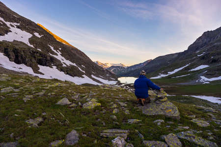 high up: One person sitting on rocky terrain and watching a colorful sunrise high up in the Alps. Wide angle view from above with glowing mountain peaks in the background. Summer adventure and exploration.