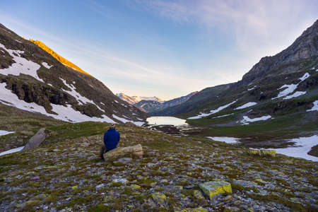 the one person: One person sitting on rocky terrain and watching a colorful sunrise high up in the Alps. Wide angle view from above with glowing mountain peaks in the background. Summer adventure and exploration.