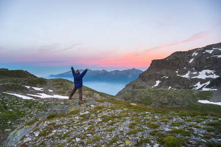the one person: One person standing on rocky terrain and watching a colorful sunrise high up in the Alps. Wide angle view from above with glowing mountain peaks in the background. Summer adventure and exploration.