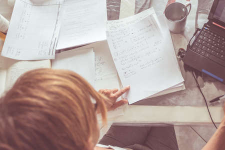 directly above: Woman sitting at desk in front of laptop, reading mathematics formula on white paper. Empty mug and many sparse documents on the table. Shot directly above, selective focus on paper. Toned image.