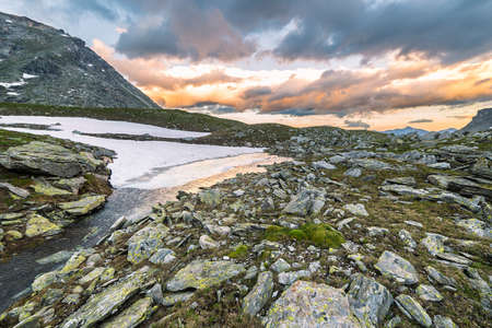 extreme terrain: High altitude alpine lake in extreme rocky terrain and uncontaminated environment. Summer adventures in the Italian French Alps. Taken at sunset with dramatic sky and colorful cloudscape.