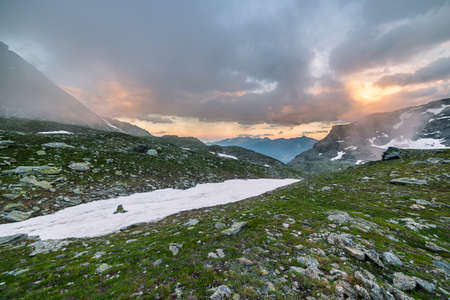 extreme terrain: High altitude alpine landscape in extreme rocky terrain and uncontaminated environment. Summer adventures in the Italian French Alps. Taken at sunset with dramatic sky and colorful cloudscape. Stock Photo