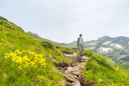 the one person: One person hiking uphill on footpath in the italian Alps. Summer adventures and exploration on the Alps. Wide angle view from below. Stock Photo