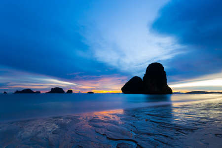 railey: Low tide with a vibrant colored sunset in the majestic scenery of Railey Bay, Krabi, Southern Thailand. Blurred motion, long exposure, erosion chutes in the foreground.
