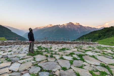 high up: One person standing on terrace and watching a colorful sunrise high up in the Alps. Wide angle view from above with glowing mountain peaks in the background. Summer adventure and exploration.