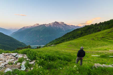 high up: One person standing on grassy terrain and watching a colorful sunrise high up in the Alps. Wide angle view from above with glowing mountain peaks in the background. Summer adventure and exploration.