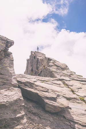 the one person: One person standing on steep rocky mountain summit. Summer adventures in the Alps. Concept of reaching the goal and conquering the success. Marsala toned filter applied.