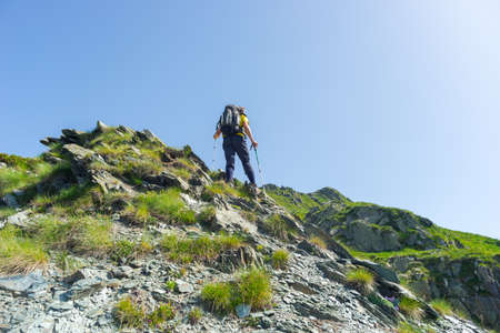 conquering: One backpacker hiking uphill on steep rocky slope towards the mountain summit. Concept of reaching the goal and conquering the success. Summer adventures and exploration on the Alps.