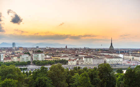 romatic: Sunset on Torino (Turin), Piedmont, Italy. Panoramic cityscape from above with Mole Antonelliana towering on the city and romatic colorful sky. Summer adventures in italian historical towns.